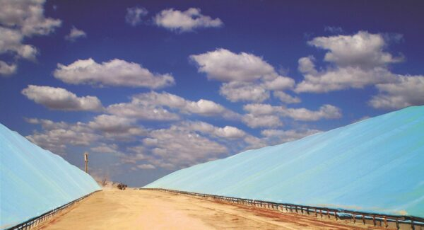 Two grain bunkers covered with ice blue tarps on a fine, blue skied day with some white clouds.