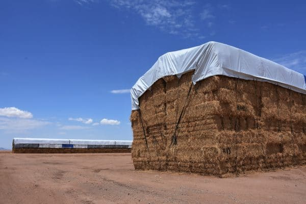 Two long square hay bale stacjs with hay tarps