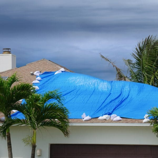 House covered with a weather proof blue roof tarp