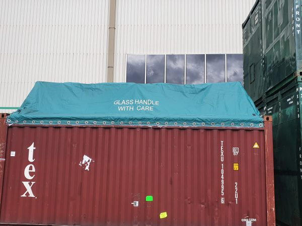 Shipping container covered with a dark aqua blue tarp with eyelets