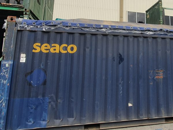 Shipping container covered by a blue tarp with eyelets