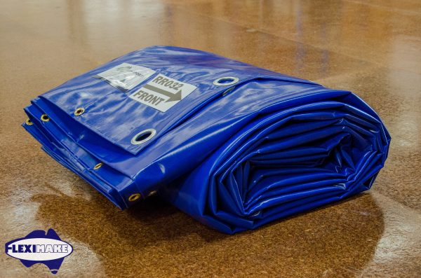 Rolled up blue container tarp with eyelets