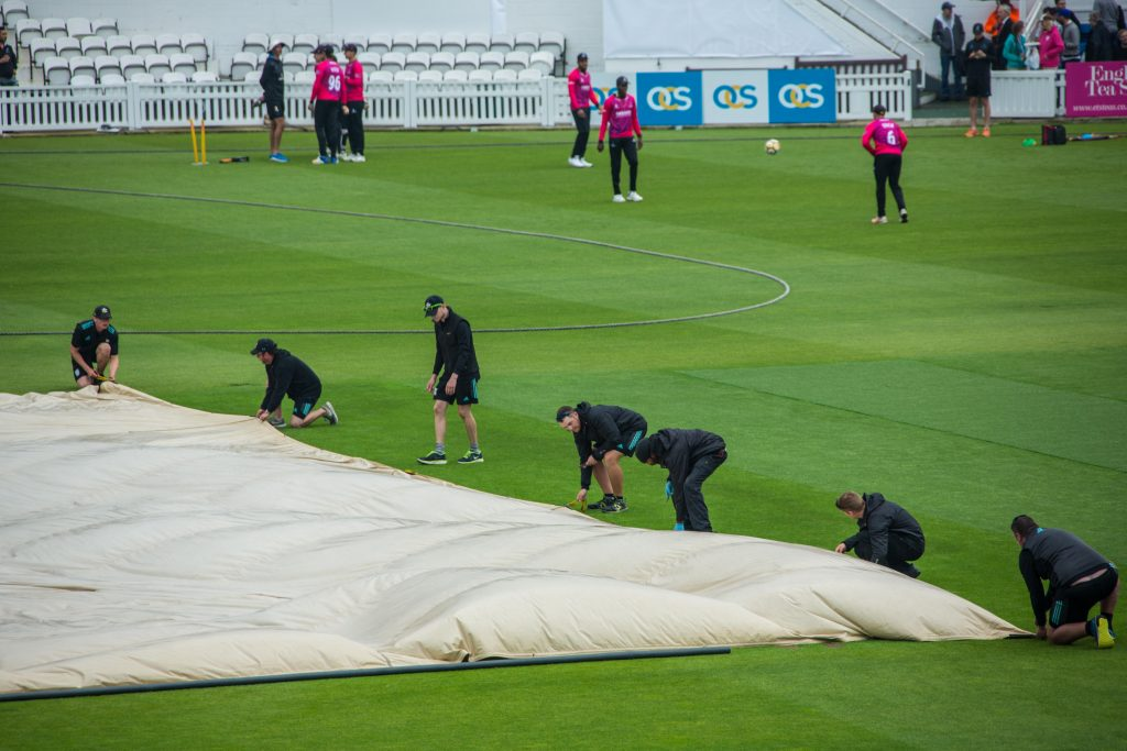 Players putting on the cricket pitch cover on the ground