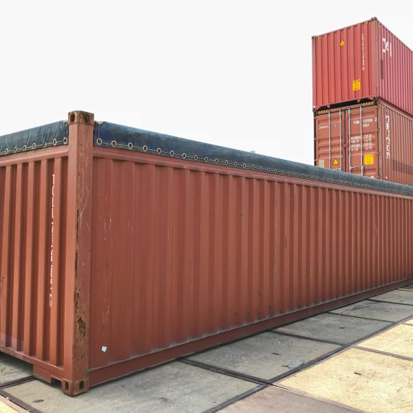 Shipping container covered by a black tarp