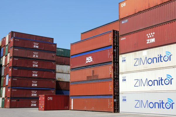 Stacked shipping containers covered by container tarps