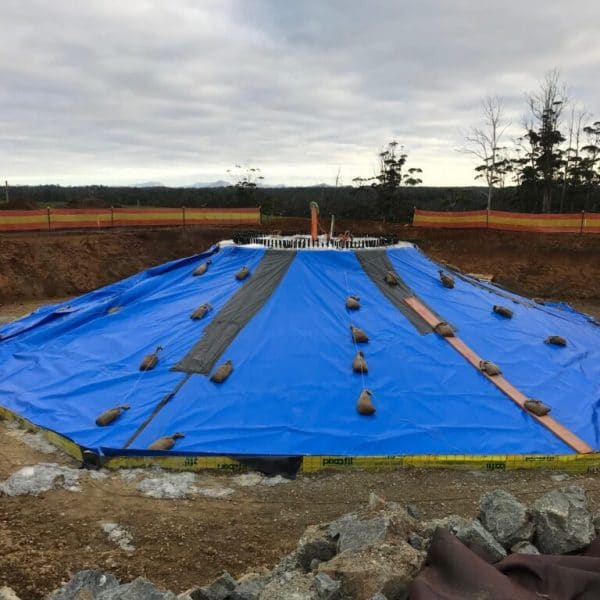 Custom made concrete blankets used for curing concrete foundation of a wind turbine during winter, with weights to stop the wind from blowing the blankets away